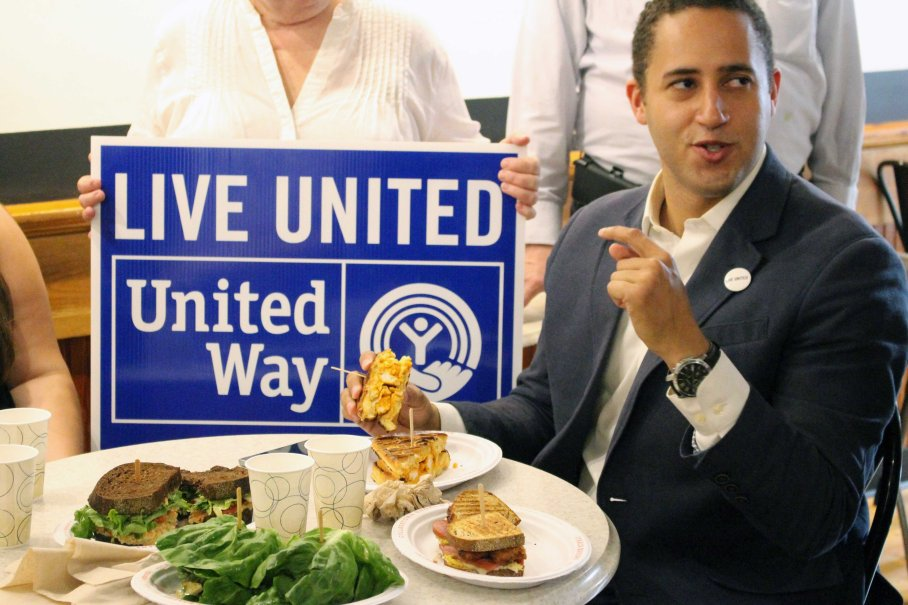 "Ithaca Mayor Svante Myrick selects the 2016 Hunger Hero sandwich, ""The Nessa."" On the menu at Ithaca Bakery and Collegetown Bagels, a portion of proceeds go to support the Tompkins County United Way."